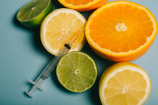 Picture of oranges, limes and lemons with a needle and syringe